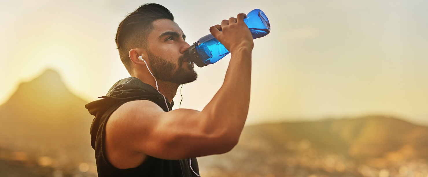 fit man drinking water outside after hot workout