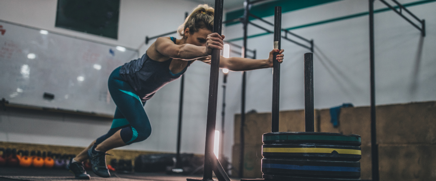 fit woman pushing weighted sled