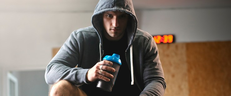 forms of caffeine: man in hoodie drinking out of sports bottle at gym