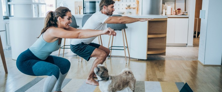 engage your glutes: couple doing squats at home with dog