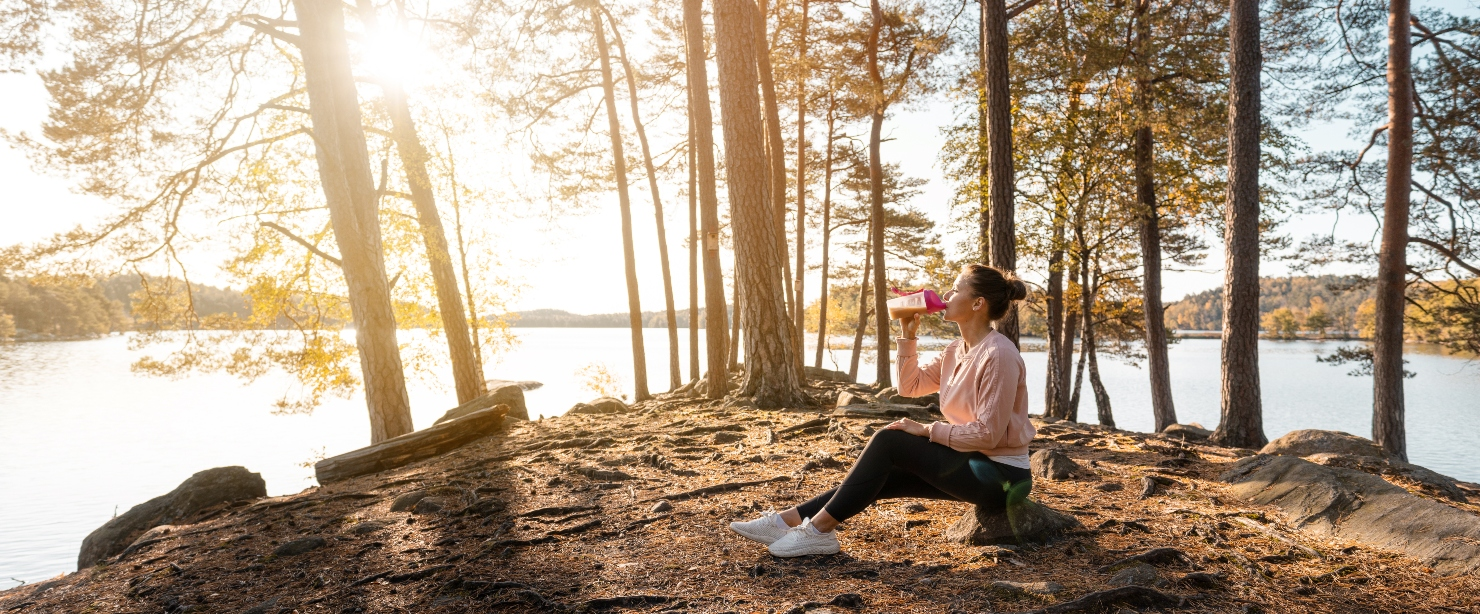 woman drinking protein shake outside by water