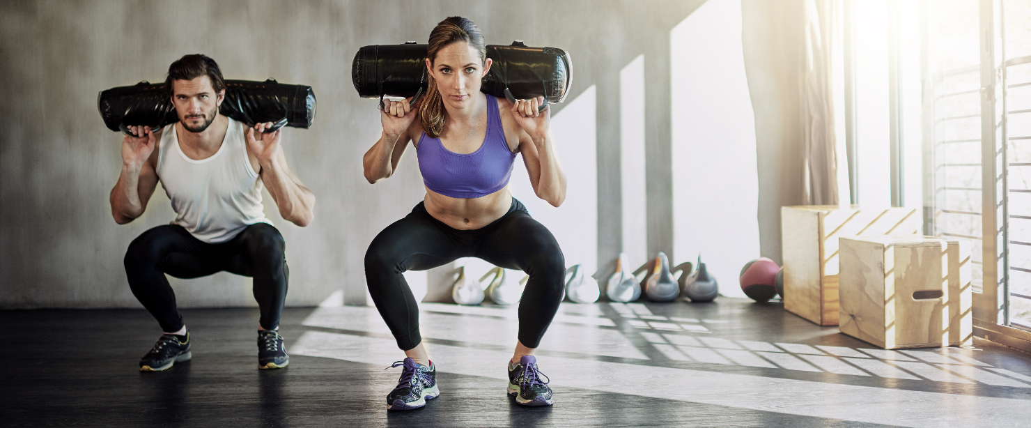 stop skipping workouts: couple working out with sandbags