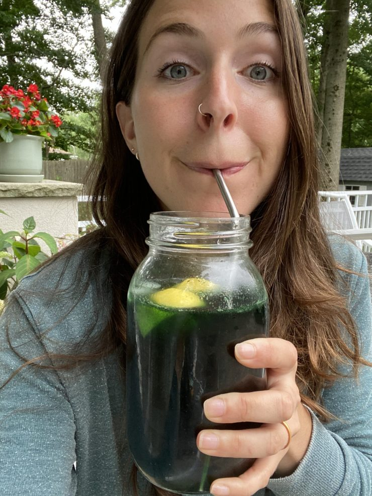 selfie of smiling girl drinking water with chlorophyll in it