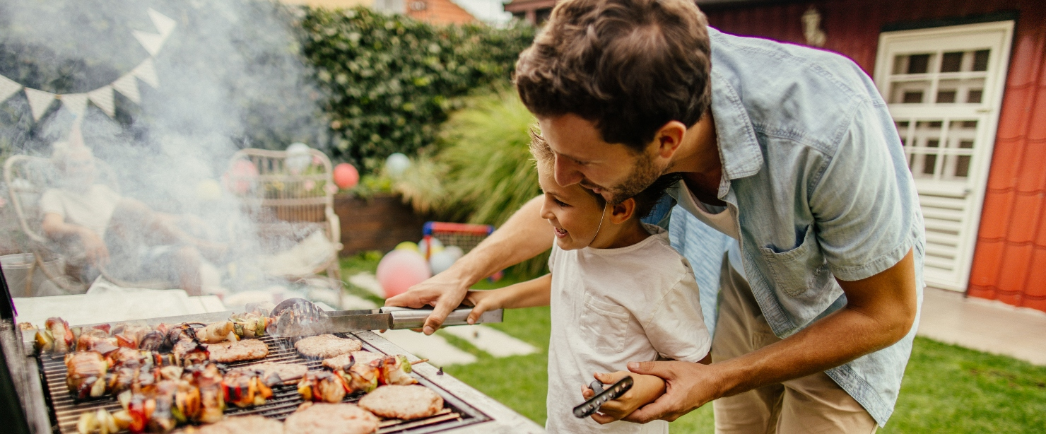 father and child grilling outside