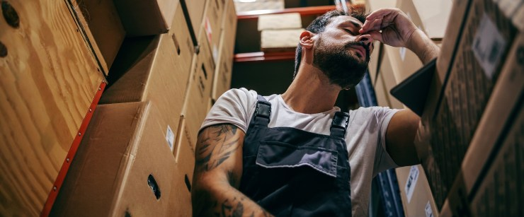 supplements for fatigue: tired man at work in warehouse
