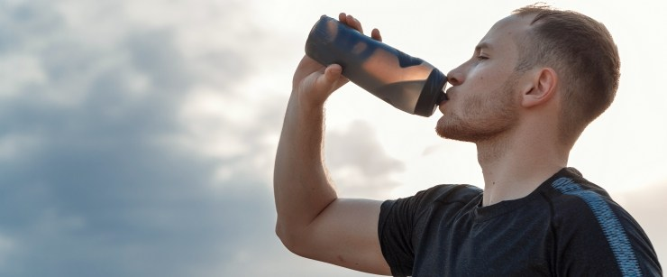 supplement with creatine: young man drinking water bottle outside