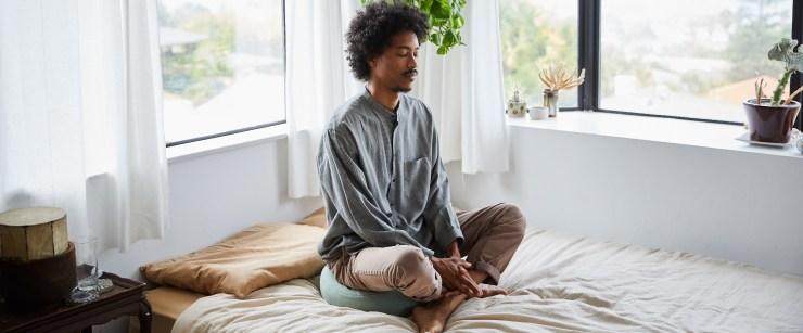 sensitive nervous system: young man meditating in bed