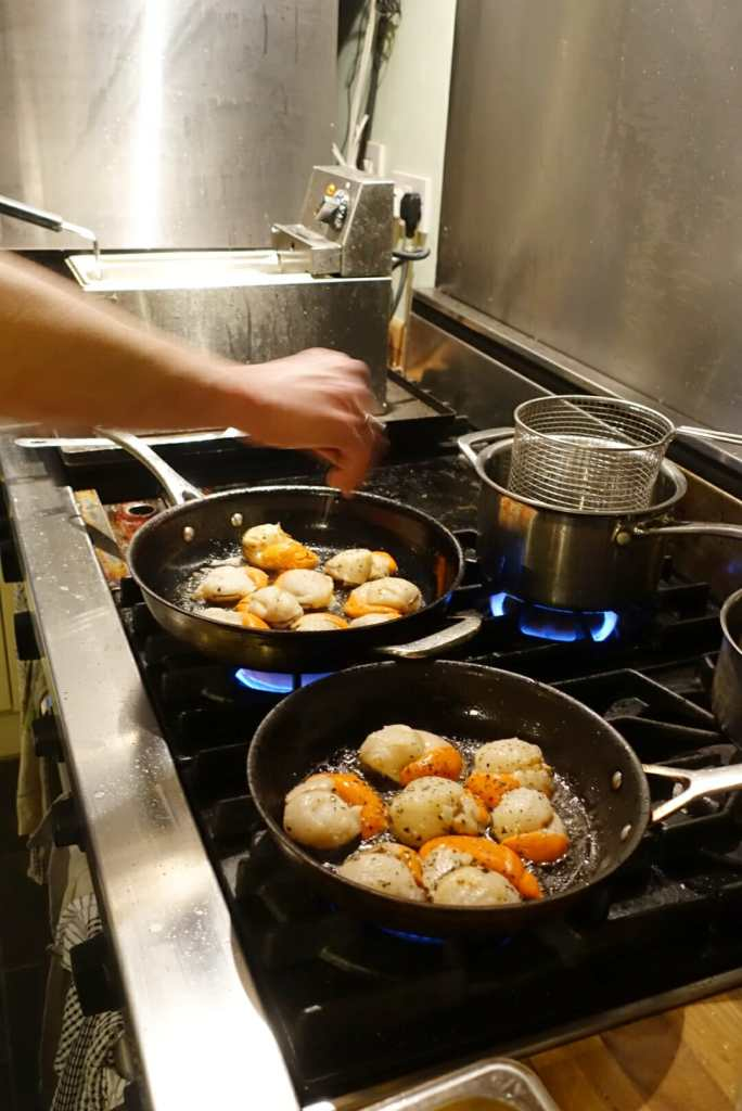 Scallops cooking in pans in the kitchen