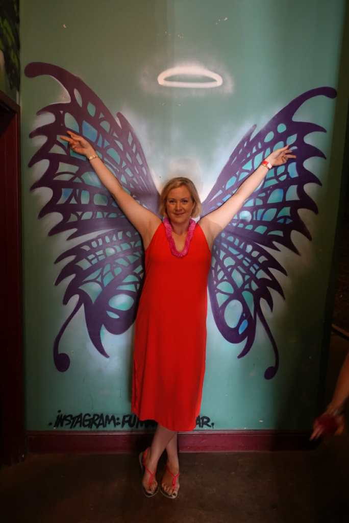 Katie in front of a wall with wings painted on it