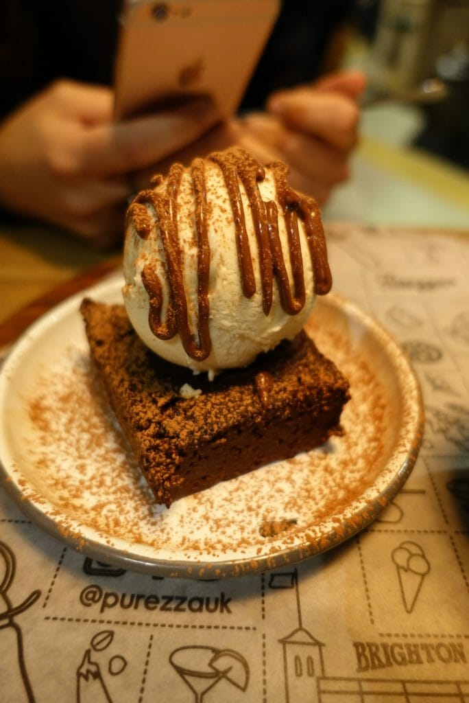 Close up of the chocolate brownie with phone taking a picture behind it