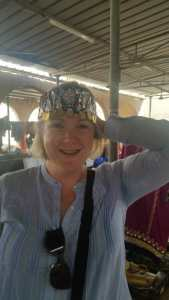 Katie modelling an embroidered headdress at Ibra women's market