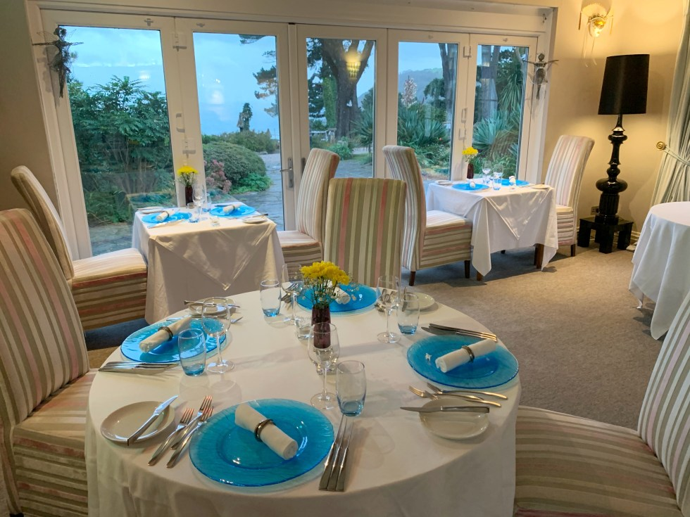 The formal dining room at Talland Bay Hotel with blue plates set out