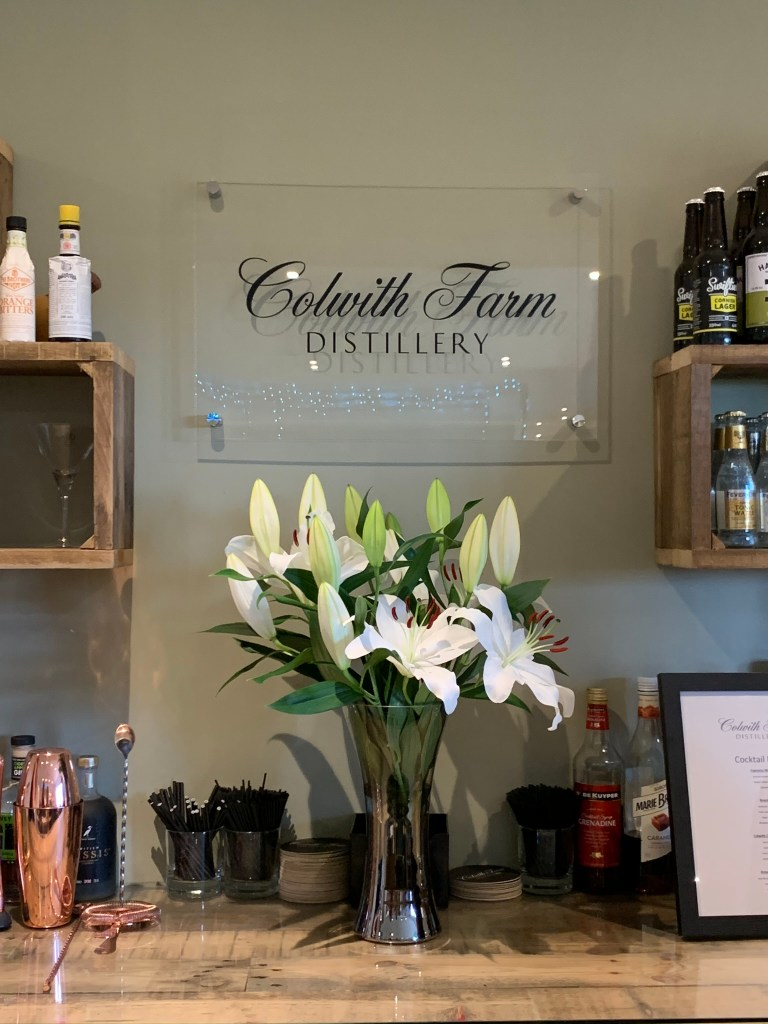 The bar area with lillies at Colwith Farm Distillery