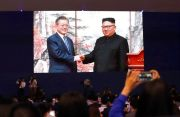 (AP Photo/Lee Jin-man). Members of media and volunteers watch a huge screen showing South Korean President Moon Jae-in, left, shake hands with North Korean leader Kim Jong Un after a joint press conference in Pyongyang, North Korea, at a press center f...