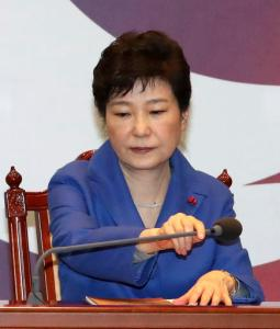 South Korean President Park Geun-hye adjusts a microphone during an emergency Cabinet meeting at the presidential office in Seoul, South Korea, Friday, Dec. 9, 2016. South Korean lawmakers earlier on Friday impeached Park, a stunning and swift fall for the country's first female leader amid protests that drew millions into the streets in united fury. (Baek Sung-ryul/Yonhap via AP)