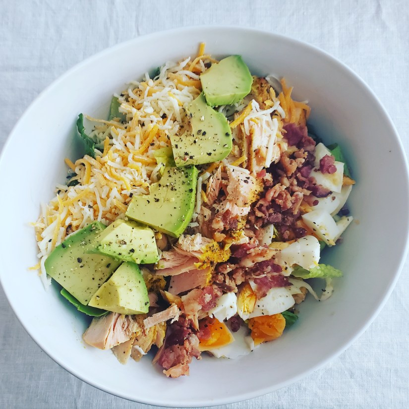 white bowl with romaine lettuce topped with salmon, cheese, bacon, boiled egg, and avacado