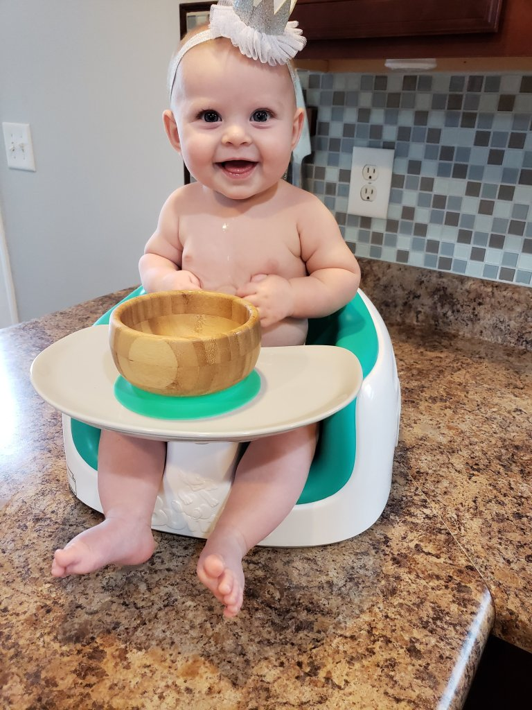 baby sitting in highchair smiling with wooden bowl