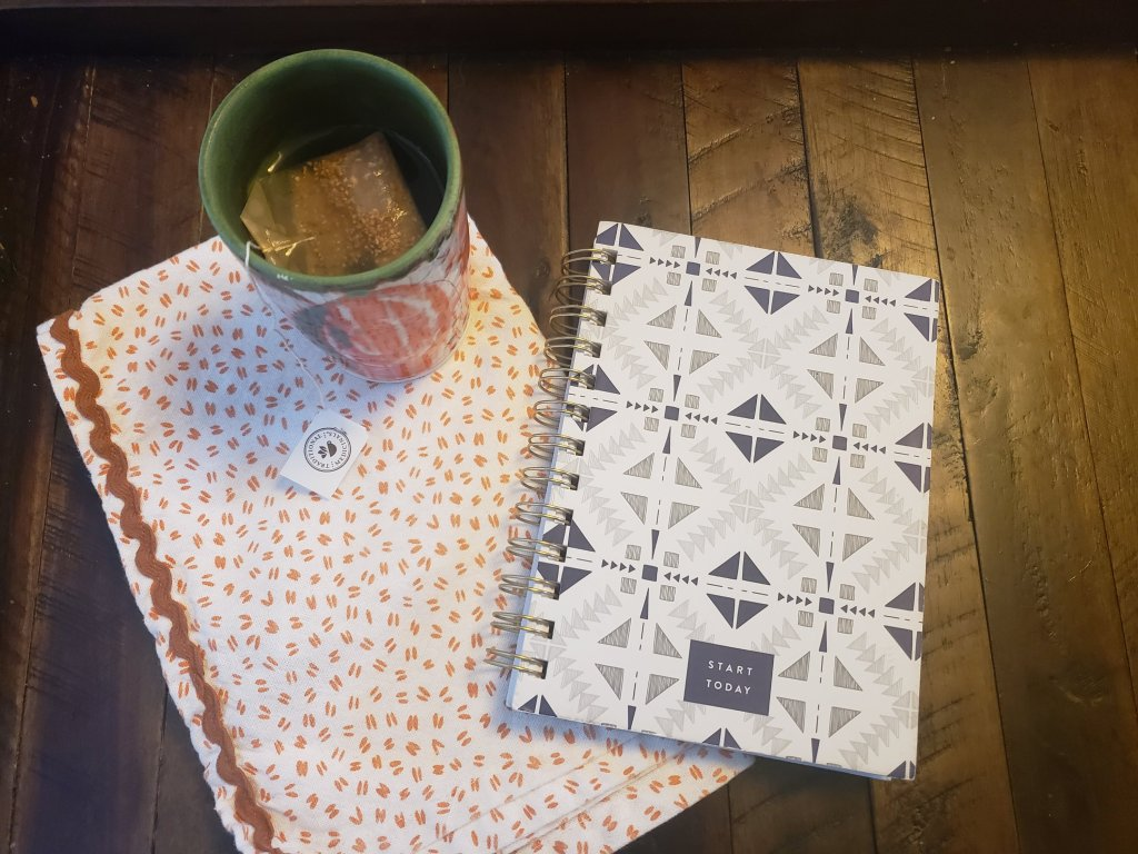 wooden table with dishcloth cup  of tea and a notebook