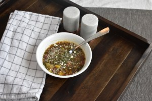 Wooden tray on a table with a white and gray checked dish towel.  A salt and pepper shaker and a bowl of vegetable soup.
