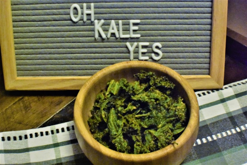 wooden tray with a letter board stating oh kale yes a dish towel with a wooden bowl that is filled with kale chips