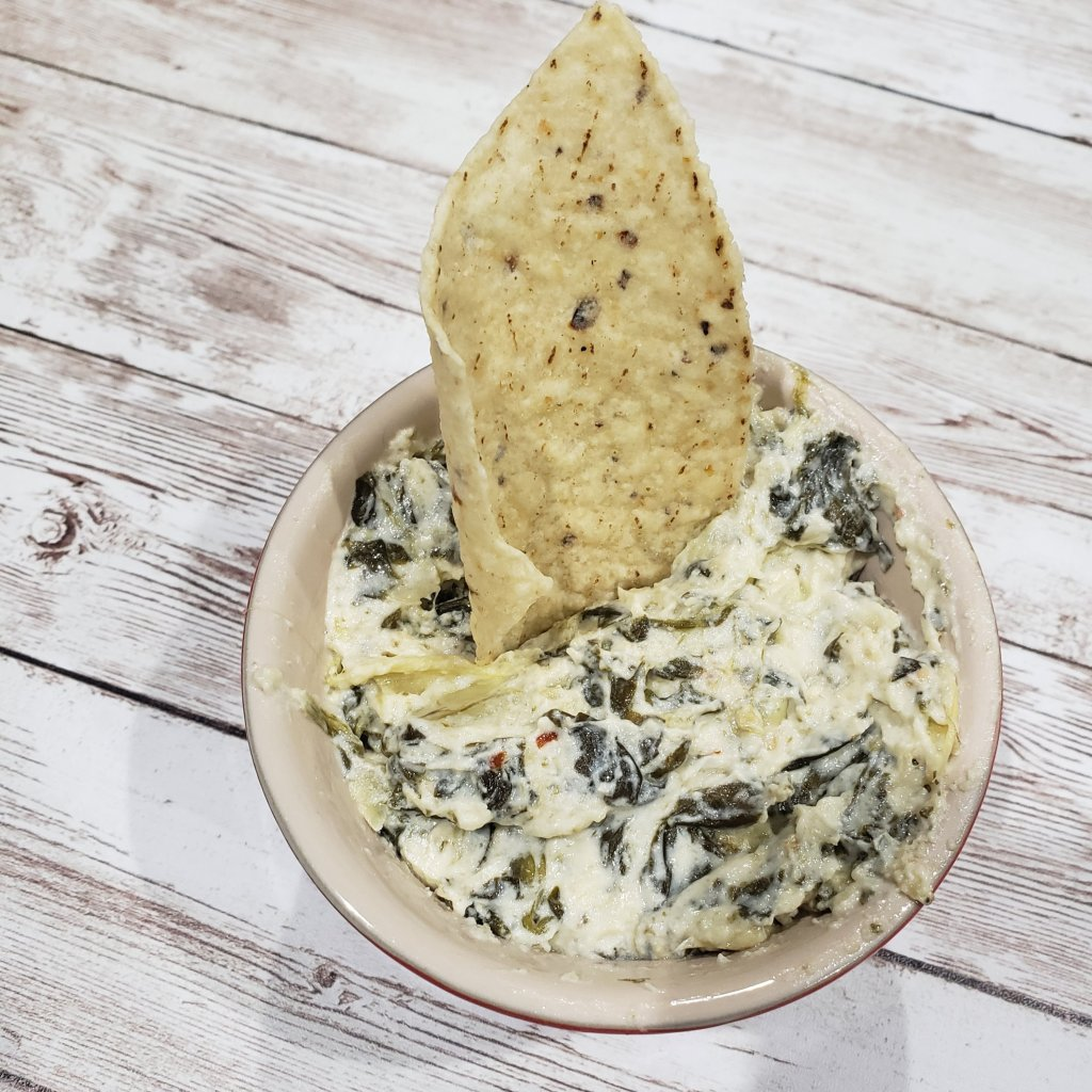 spinach artichoke dip in a bowl on a wooden table with a tortilla chip in it
