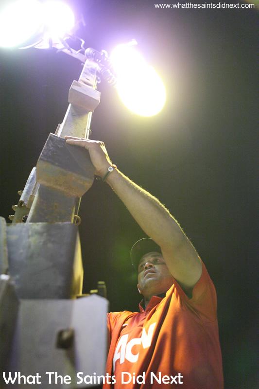 Football on St Helena under floodlighting, fixing the lights.