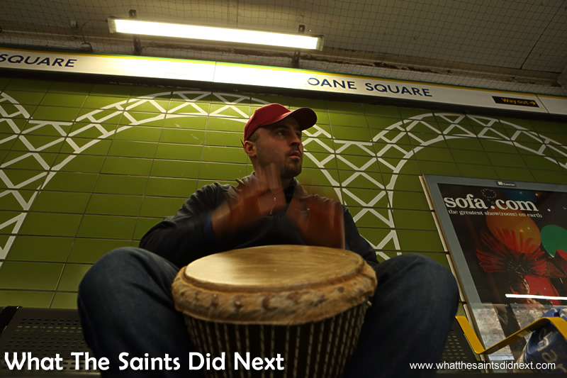 Banging the drum in Sloane Square underground station. Homeless Bucket Drum Busker Living On The Streets Of London.