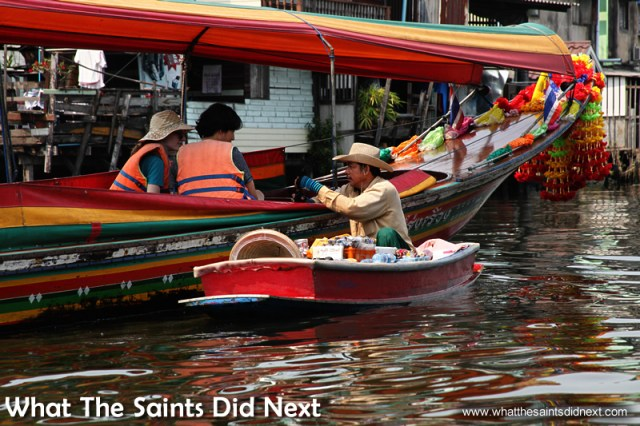 Another long tail boat gets a visit from a floating seller. Bangkok Long Tail Boat Tour.