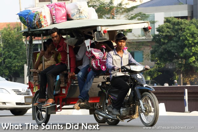 The flat terrain allows the mopeds to pull all manner of heavily laden trailers in Cambodia. Watching Cambodia Traffic.