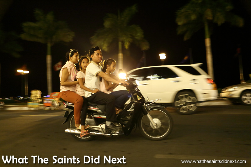 A family out for the night, cruising through the Riverside in Phnom Penh. Watching Cambodia Traffic.