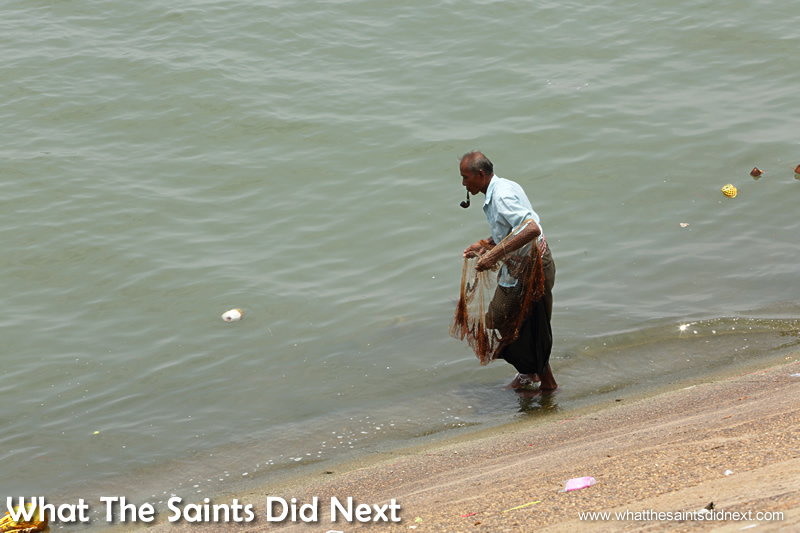 A man fishing in the river below the shrine. Our first time in Phnom Penh exploring the city.