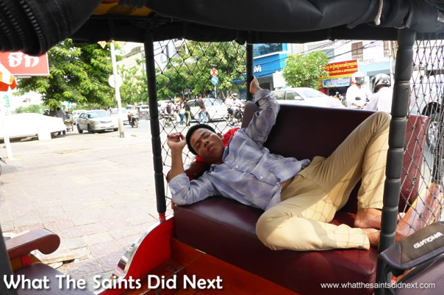 Sleeping tuk tuk driver in the back of his 'taxi.' Walking The Streets Of Phnom Penh.