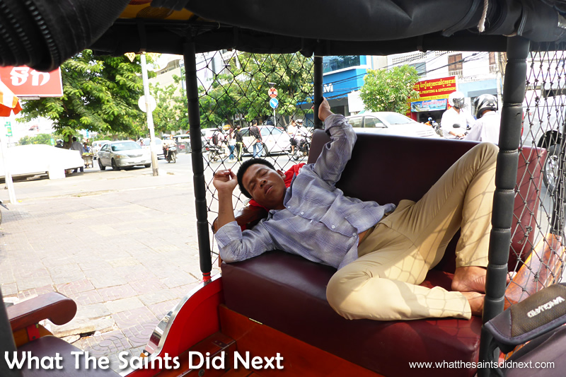 Sleeping tuk tuk driver in the back of his 'taxi.'