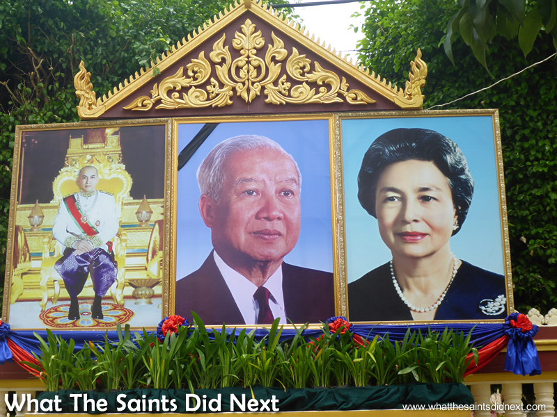 Portraits of King Norodom Sihamoni and his parents outside the Royal Palace walls.