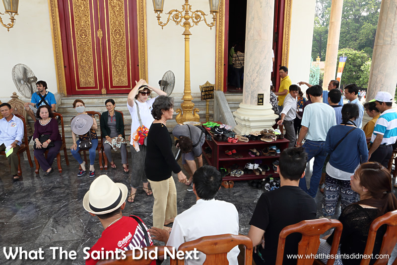 Visitors removing their shoes before entering inside the Phnom Penh Silver Pagoda, Royal Palace.
