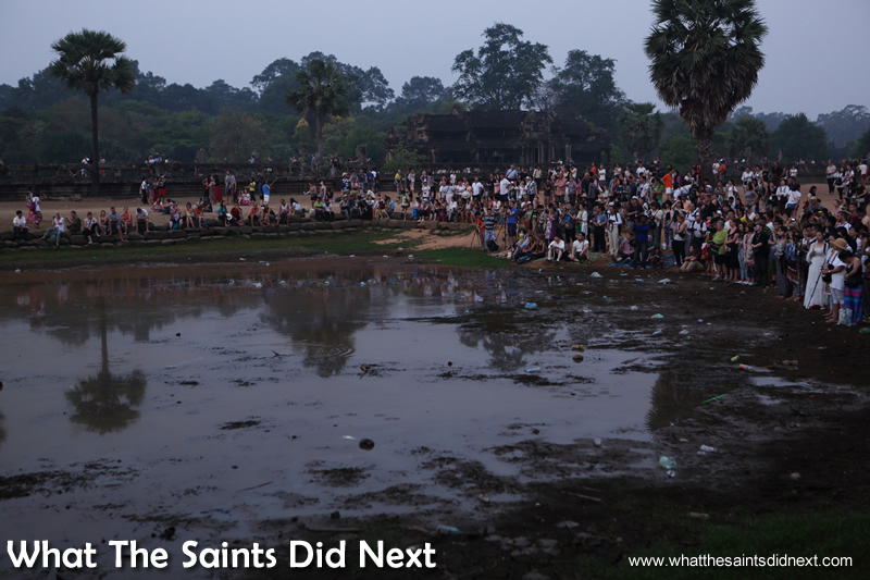 The muddy puddle of a 'reflecting' pool at Angkor Wat with crowds of early birds at the front.