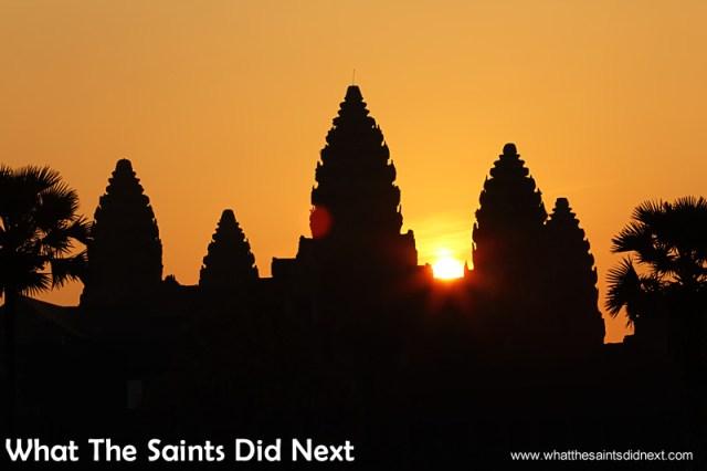 The magic moment as the sun peeks through the Angkor Wat towers.  Watching an Angkor Wat sunrise.