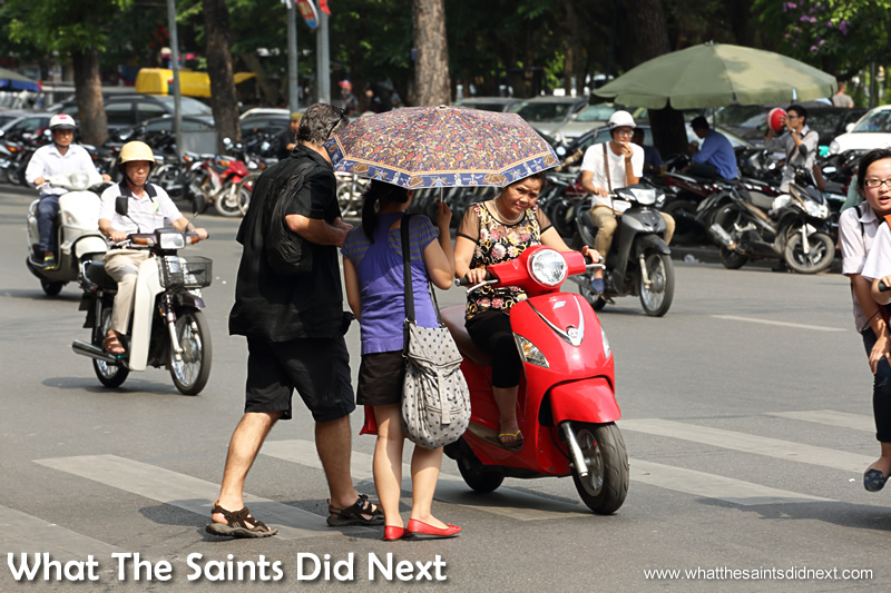 This moped driver passed so close to this couple the driver had to duck under the umbrella. Crossing The Street In Hanoi Vietnam.