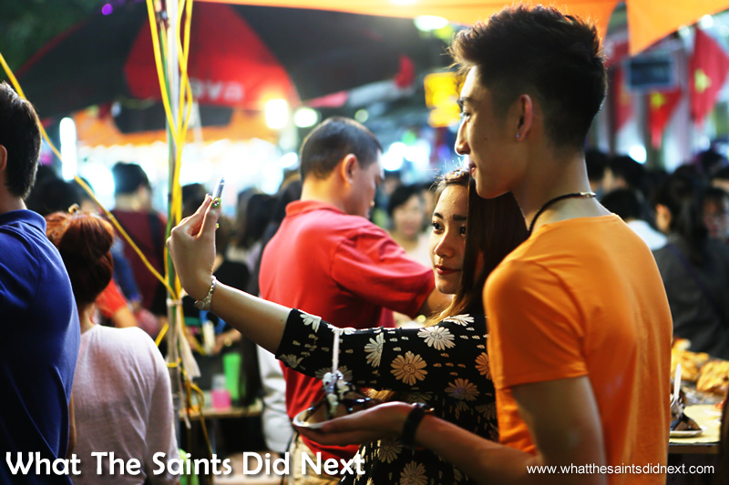 Selfie time is any time. Young people enjoying the Hanoi night market.