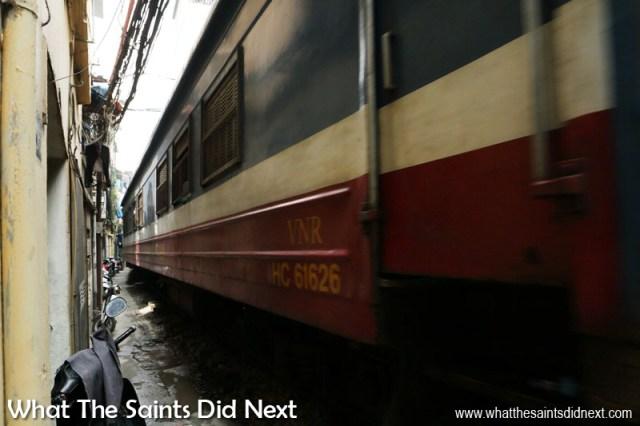 The train through Hanoi, Vietnam. Up close as the carriages whiz by. Train track running through the narrow Train Street in Hanoi.