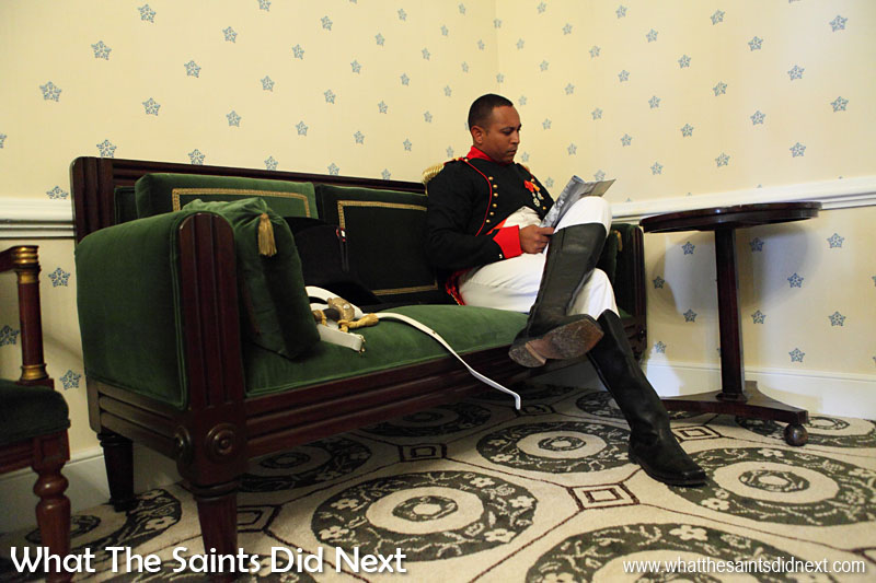 'Napoleon' reading in Longwood House. The scene in 1815 would have been very similar as the room has been restored as accurately as possible to that period, including custom made replica carpet and wallpaper and with authentic furniture pieces. This staged scene is all part of the Bicentenary re-enactment on 10 December 2015, of Napoleon Bonaparte arriving at Longwood House for the first time. The real Napoleon took up residence on 10 December, 1815. St Helena exile Napoleon Bonaparte.