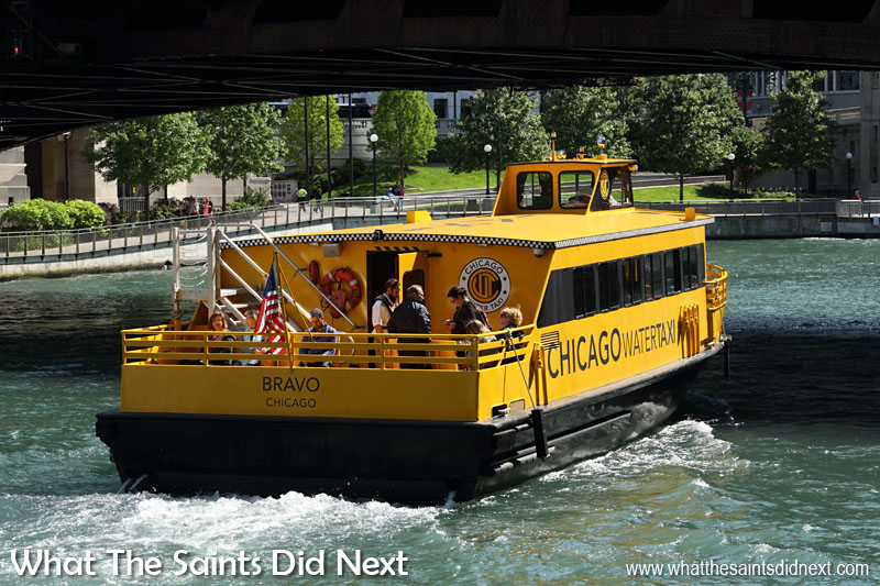 A Chicago water taxi passing under one of the many movable bridges in the Loop District of downtown Chicago.