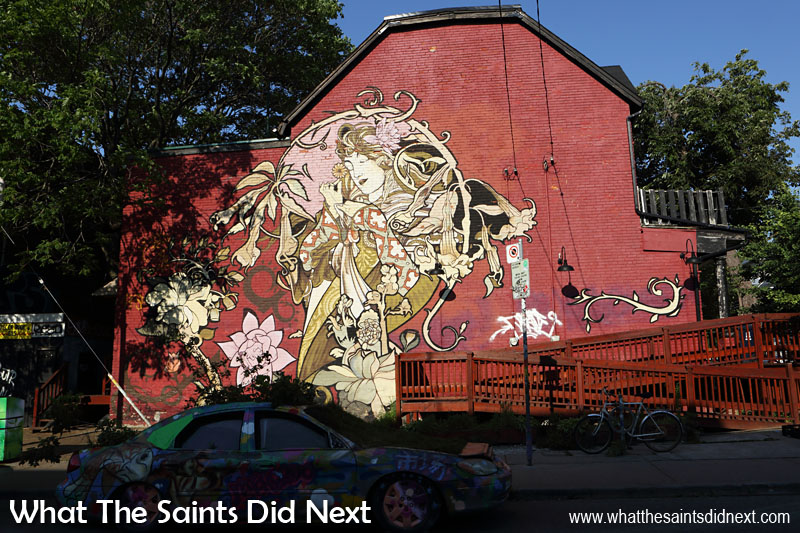 Graffiti in Toronto - This mural of a flower lady was the biggest we saw and the most beautiful. One of the best graffiti art murals in Kensington Market. She is stood next to the 'garden car.'
