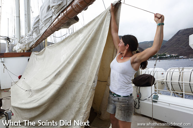 One of the ship's crew, Becca, sorting out sails on the upper decks of Gulden Leeuw. A rainy St Helena can be seen in the distance. It did get better during the day!