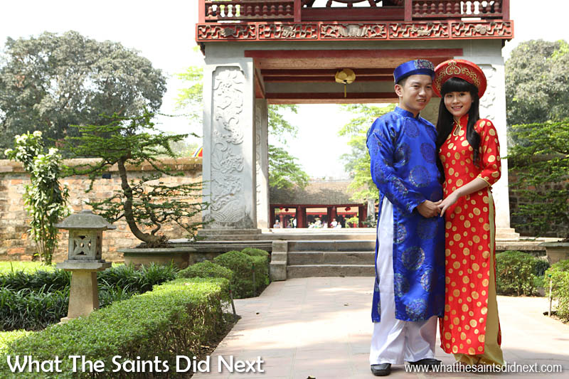 Young Vietnamese couple posing for photos in the Temple of Literature wearing traditional dress, possibly on a pre wedding photoshoot.
