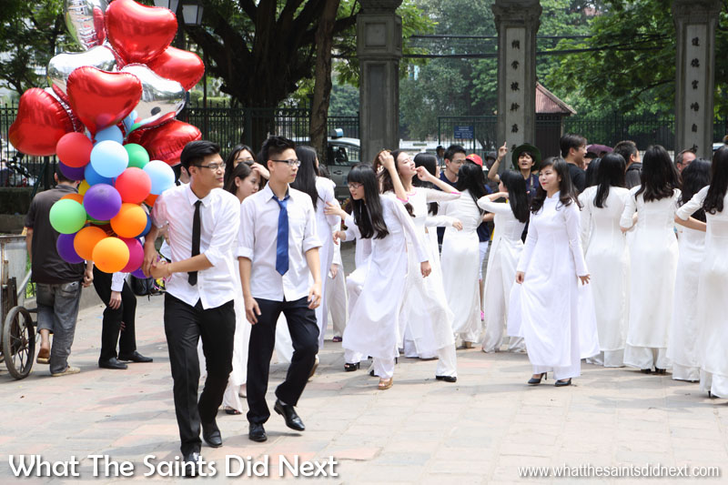 Vietnamese students arrive for traditional good luck blessings at the Quoc Tu Giam. They brought contrasting colourful balloons. Excellent for photographs.