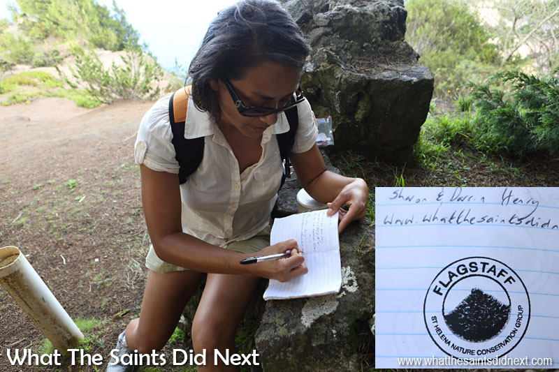 Flagstaff Post Box walk - Sharon writing in the visitors' book at the top. The pipe on the left is the actual 'Post Box' where you will find the book and stamp. Most of the post boxes on St Helena have a similar setup.