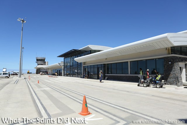 The brand new St Helena Airport terminal under a brilliant blue Atlantic sky. The arrivals hall is nearest the camera, the departures lounge is on the other side of the glass viewing deck. The control tower and Combined Building is at the far end.