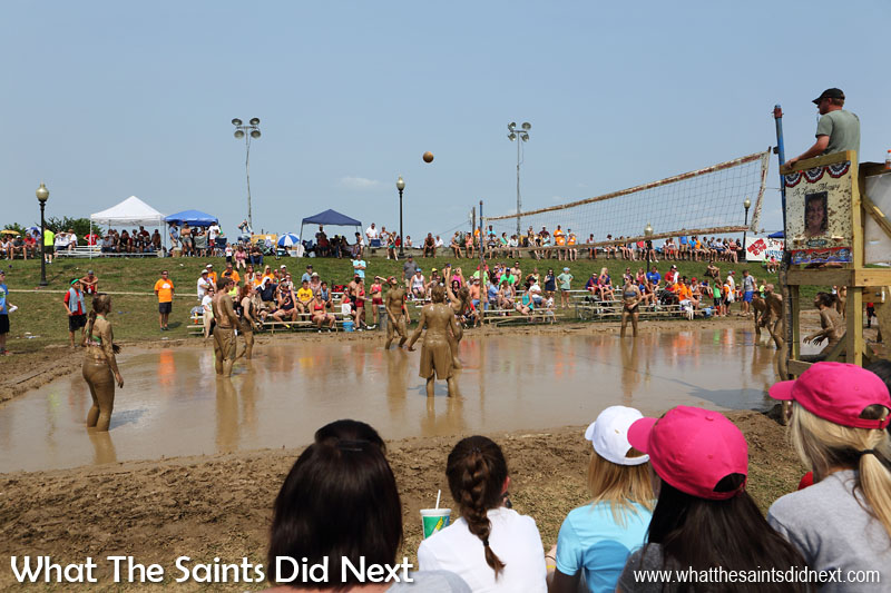 Annual Mississippi Mud Volleyball Tournament underway in Hannibal, Missouri. Surprisingly, the spectators stit quite close without getting 'splashed' as the thick mud doesn't fly too far. The Mississippi River is directly behind the grassy bank at the back of the photo.