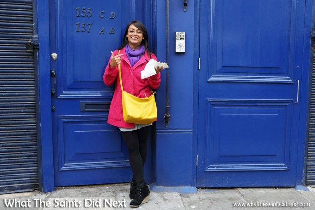 How To Make Better Use of Colour In Photography - Once you begin to be more aware of colours around you then ideas for creative photography kick in. These blue doors along Portobello Road, London, needed a little contrast to set them off and Sharon had obviously gotten the 'wear colour' memo that morning! Pink, yellow, purple and blue - not holding anything back with this one. Colour photography tips.